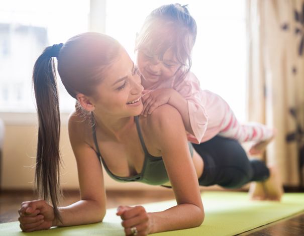 Woman exercising with daughter on back