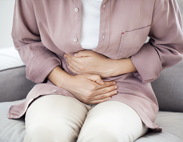 Woman holding her stomach - Constipation