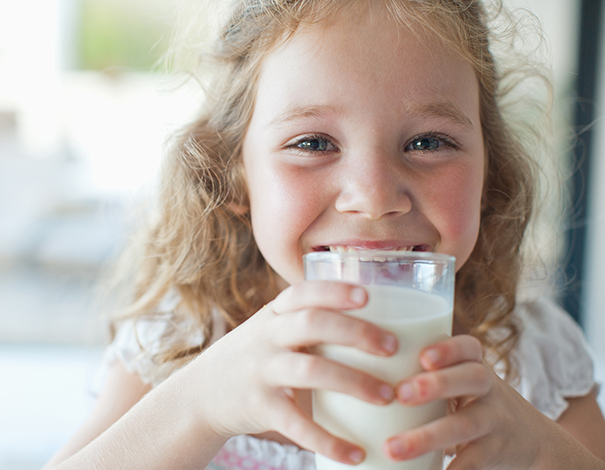Little girl drinking a glass of milk while smiling - lactose intolerance