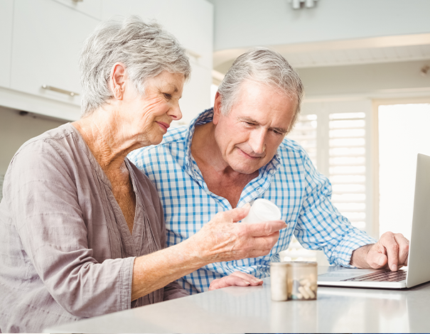 Elderly man and woman studying vitamin bottle